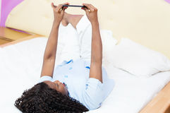 Young woman lying on the bed  using a mobile phone Stock Photo