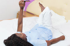 Young woman lying on the bed  using a mobile phone Stock Photos