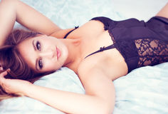 Young woman lying in bed wearing lingerie Royalty Free Stock Image