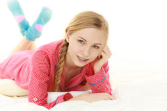 Young woman lying on bed wearing pajamas Royalty Free Stock Image