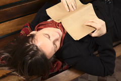 Young Woman Lying on Bench with Book Stock Photo