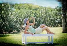 Young woman lying on bench in park Royalty Free Stock Photography