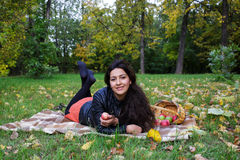 Young woman is lying on a blanket on grass in the autumn park and smiles Stock Photography