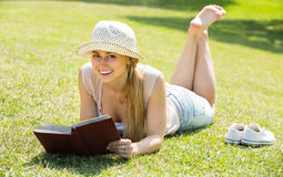 Young woman lying with book outdoors Stock Photo