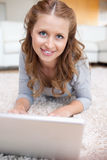 Young woman lying on the carpet with her laptop Royalty Free Stock Images