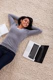 Young woman lying on carpet with laptop Stock Image