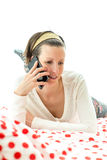 Young woman lying chatting on a mobile phone Stock Photos