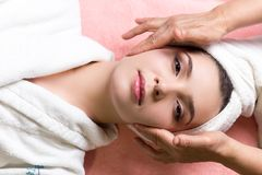 Woman lying with closed eyes and having face or head massage in spa. Young woman lying with closed eyes and having face or head massage in spa royalty free stock photos