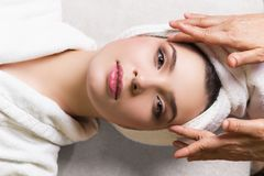 Woman lying with closed eyes and having face or head massage in spa. Young woman lying with closed eyes and having face or head massage in spa stock photography