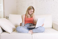 Young woman lying comfortable on home sofa using internet in laptop computer smiling happy Royalty Free Stock Images