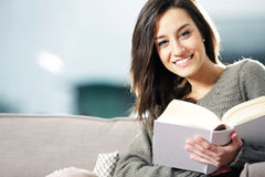 Young woman lying on couch with book Stock Image