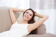 Young woman lying on couch with hands behind her head royalty free stock photography