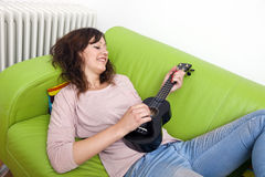 Young woman lying on couch playing ukulele Stock Images