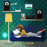 Young woman lying on the couch and reading a book Royalty Free Stock Images