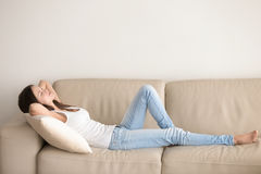 Young woman lying on couch, relaxing with hands behind head. Young woman lying on couch cushion with eyes closed, relaxing on cozy sofa pillow, relaxed girl Stock Photos