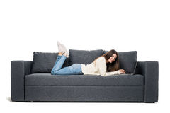 Young woman lying on couch and using laptop at home Royalty Free Stock Photo