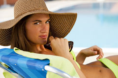 Young woman lying on deckchair by swimming-pool. Close-up of a beautiful young woman lying on deckchair by swimming-pool Royalty Free Stock Photos