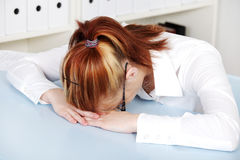 Young woman lying on the desk. Royalty Free Stock Image