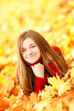 Young woman lying down in autumn leaves smiling. Young woman lying down in autumn leaves smiling stock images