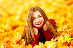 Young woman lying down in autumn leaves smiling. Stock Photo