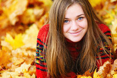 Young woman lying down in autumn leaves smiling. Young woman lying down in autumn leaves smiling royalty free stock photography