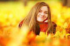 Young woman lying down in autumn leaves smiling. Young woman lying down in autumn leaves smiling stock photography