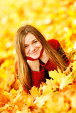 Young woman lying down in autumn leaves smiling. Young woman lying down in autumn leaves smiling stock photo