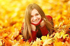 Young woman lying down in autumn leaves smiling. Young woman lying down in autumn leaves smiling royalty free stock image