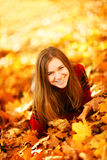 Young woman lying down in autumn leaves smiling. Young woman lying down in autumn leaves smiling royalty free stock photo