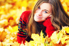 Young woman lying down in autumn leaves smiling. Royalty Free Stock Image