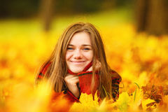Young woman lying down in autumn leaves smiling. Young woman lying down in autumn leaves smiling stock image