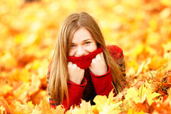 Young woman lying down in autumn leaves smiling. Royalty Free Stock Photography