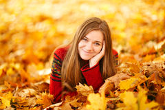 Young woman lying down in autumn leaves smiling. Young woman lying down in autumn leaves smiling royalty free stock photos
