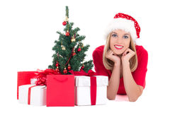 Young woman lying down with christmas tree and gifts isolated on Royalty Free Stock Photography