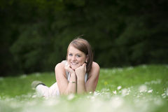 Young woman lying down in a grass with daisies Stock Images