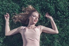 Young woman lying down on grass Royalty Free Stock Images