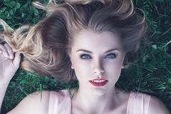 Young woman lying down on grass Stock Photos