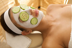 Young woman lying down on massage table with cucumbers on eyes and face Royalty Free Stock Photos