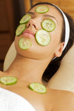 Young woman lying down on massage table with cucumbers on eyes and face Royalty Free Stock Photography