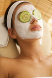 Young woman lying down on massage table with cucumbers on eyes Royalty Free Stock Photos