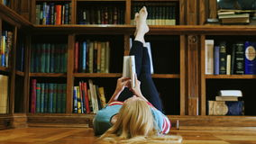 Young woman lying down reading a book. Is lying in the library stock footage