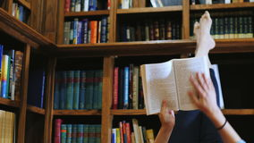 Young woman lying down reading a book. Is lying in the library stock video footage