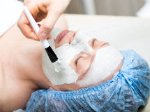 Young woman lying down in a spa salon and having a facial beauty treatment. The cosmetic procedures for the face. Beauty Stock Image