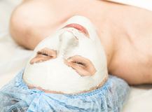 Young woman lying down in a spa salon and having a facial beauty treatment. The cosmetic procedures for the face. Beauty Royalty Free Stock Photography