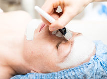 Young woman lying down in a spa salon and having a facial beauty treatment. The cosmetic procedures for the face. Beauty Stock Images