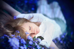 Young woman lying down in spring blue flowers. Stock Photo