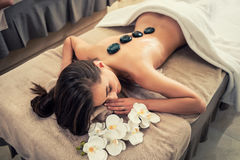 Young woman lying down with traditional hot stones along the spine stock photo
