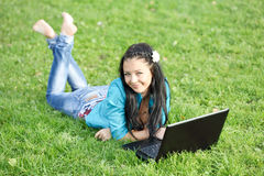 Young woman lying down using a laptop Royalty Free Stock Images