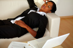 Young woman lying with eyes closed and headache. Top view portrait of a young executive woman lying on sofa with eyes closed and headache in front of her laptop Stock Photography