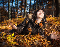 Young woman lying in fallen leaves Royalty Free Stock Photo